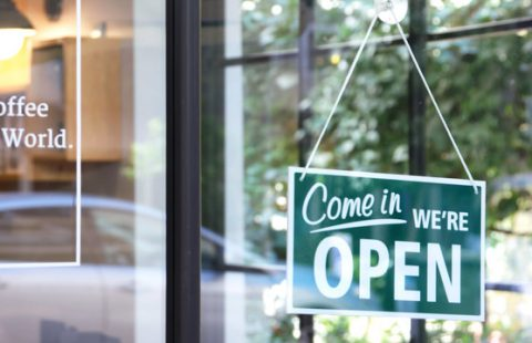 """Sign outside a small business shop saying """"come in we're open"""""""