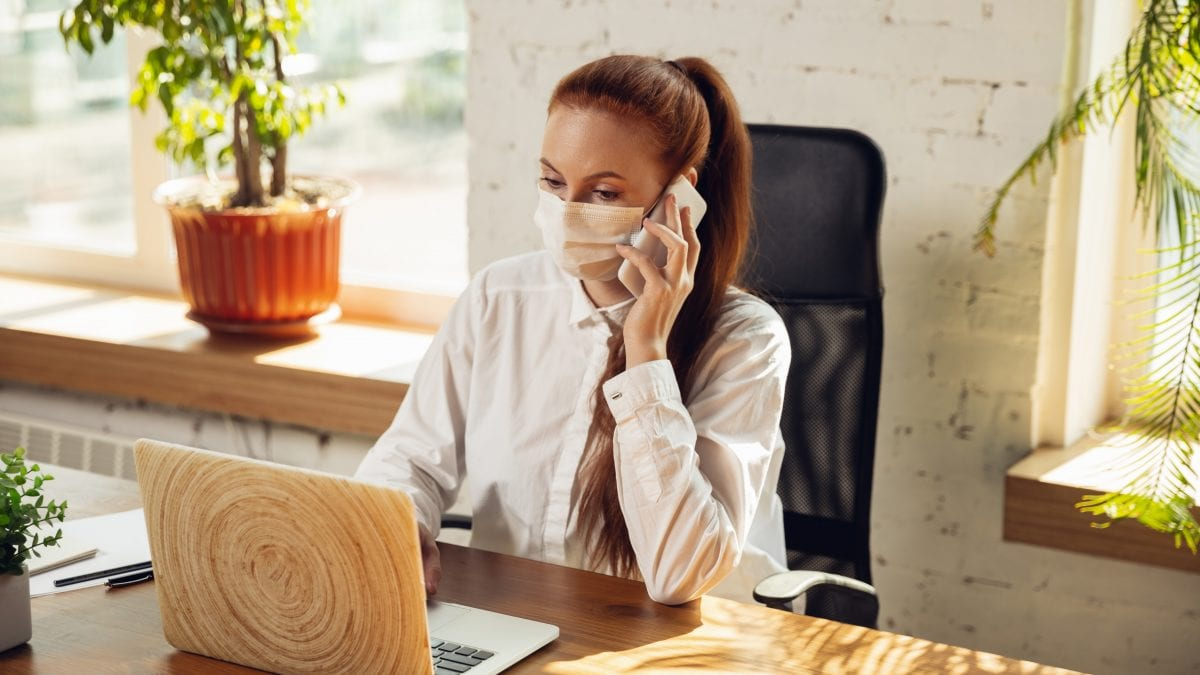 Woman working in office alone during coronavirus or COVID-19 quarantine, wearing face mask