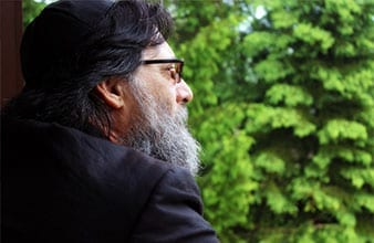 man with a beard and glasses staring out a window