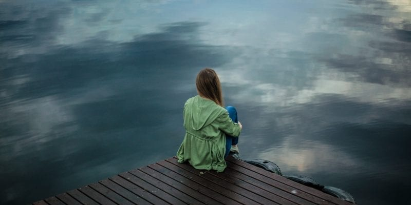 woman sitting on dock looking out over the water