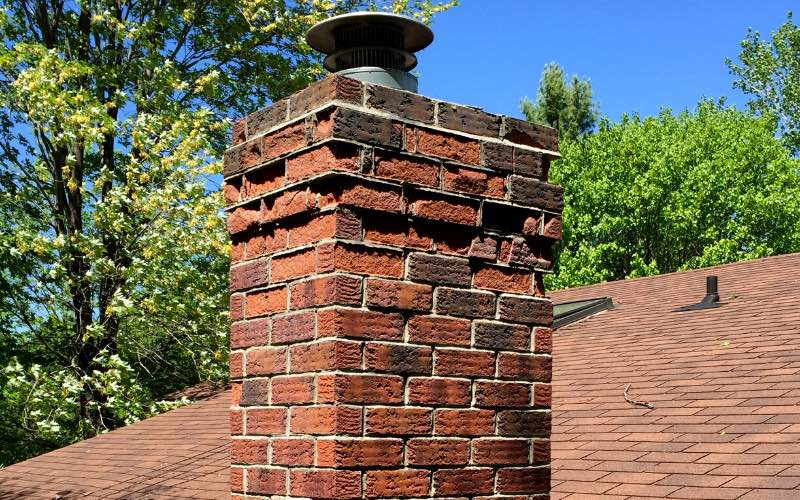 Close up of the top of a brown brick chimney