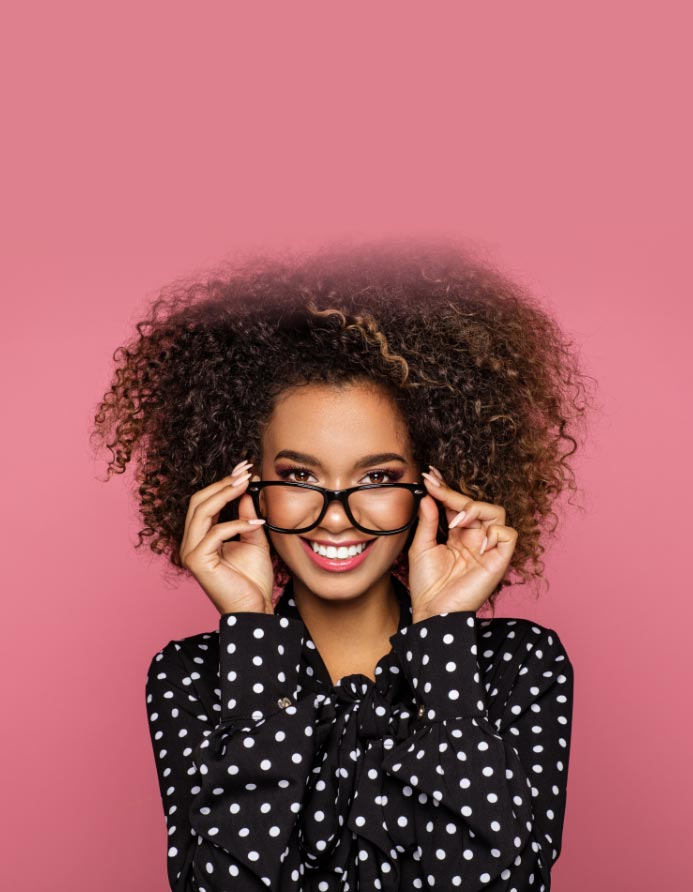 woman holding up glasses on her face infront of a pink background