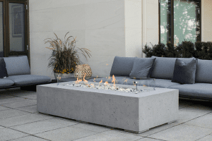 Outdoor fire pit on a patio surrounded by couches in a