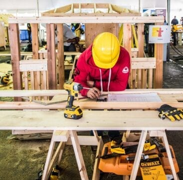 Construction worker leaning over a wooden table