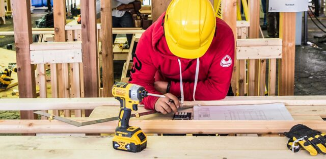 Carpenter with a yellow hard hat leaning over a wooden table with construction tools