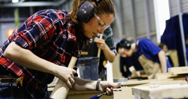 Woman wearing safety goggles and ear plugs, working on a construction project