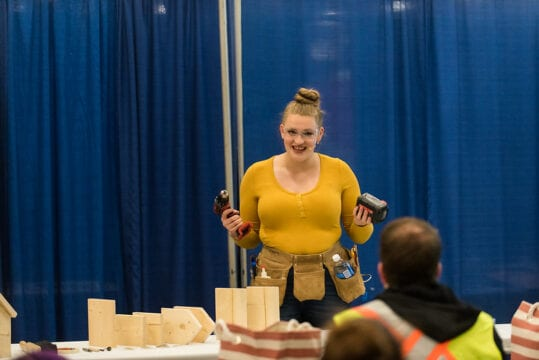 A woman demonstrating different wood working tools in front of an audience