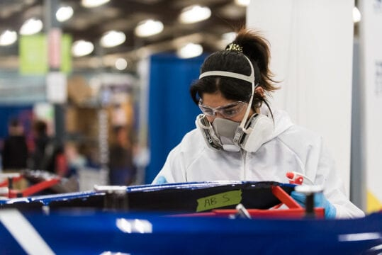 A woman wearing a face mask and safety goggles while repairing an automobile