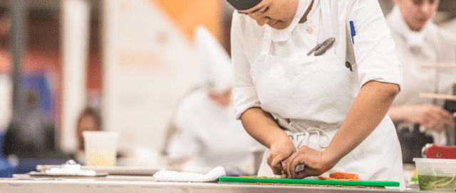 A chef using cooking tools on a vegetable cutting board